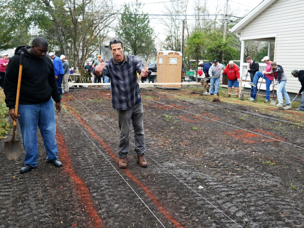 Eric Clemmer, construction site supervisor for Cape Fear Habitat for Humanity, shows volunteers where to dig.