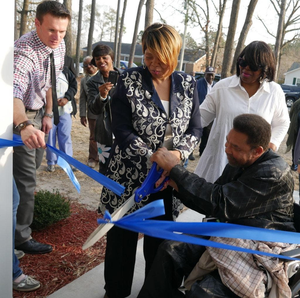Bobby McDonald cuts the ribbon of his and Regina's new home. At left is Matthew Whittle, executive director of Habitat for Humanity of Goldsboro-Wayne.