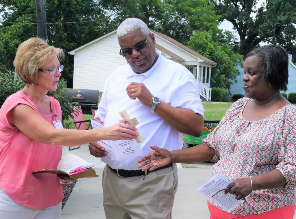 Cemita Gibbs, left, executive director of the Stanly County Habitat for Humanity affiliate, presents a cross to Greg and Mechelle Goins during the dedication ceremony.