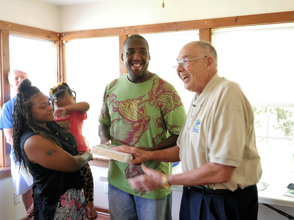 David Johnson, a board member of Chowan/Perquimans Habitat for Humanity, hands a family Bible to Ryan Harris. On the left are Qunita Williams and Ry' Milliya Harris, 3.