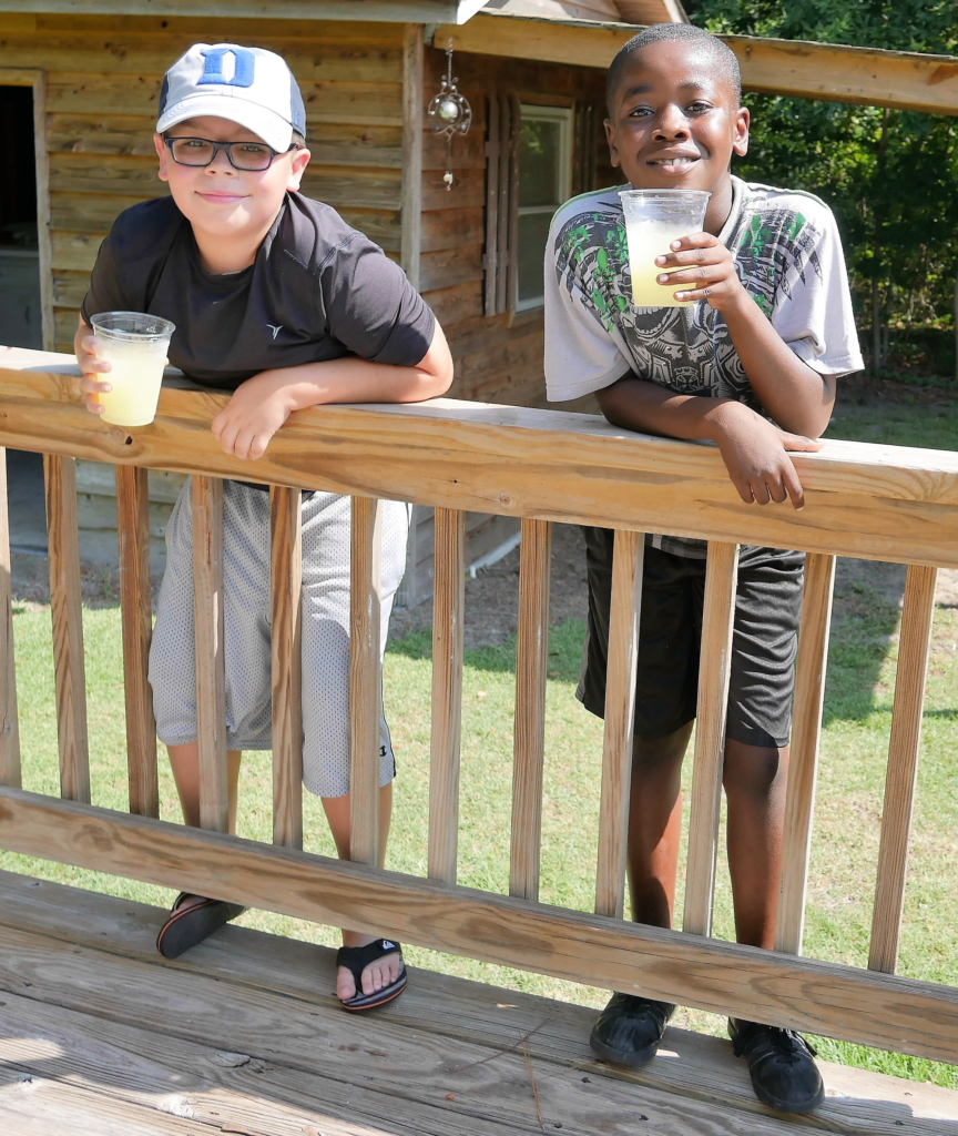 Sam Clifton, left, and Kaleb Harris, fifth-grade friends, on the back porch during the house dedication. Kaleb is Ryan Harris's nephew.