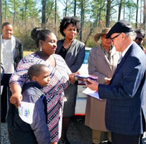 The Rev. William Reid of Meherrin Native American Church hands a Bible to Shavonda Smith at the dedication of her new Habitat for Humanity home in Ahoskie.