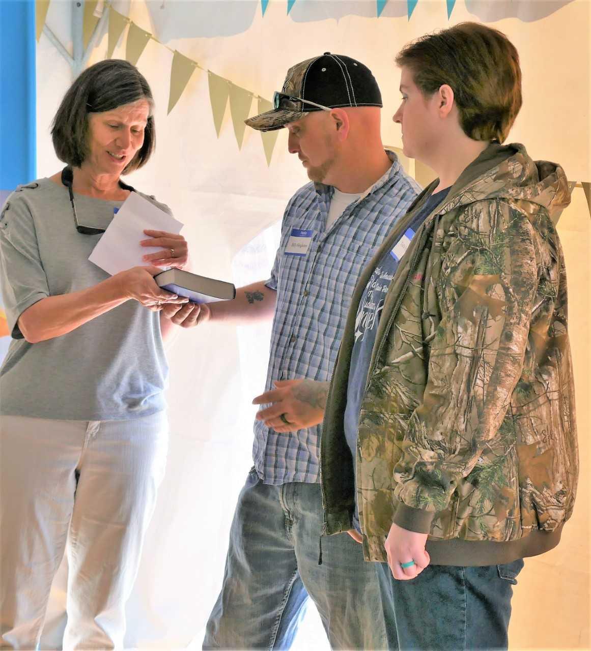 Beth Huggins, a Habitat for Humanity volunteer, presents a Bible to Billy and Tasha Singleton.