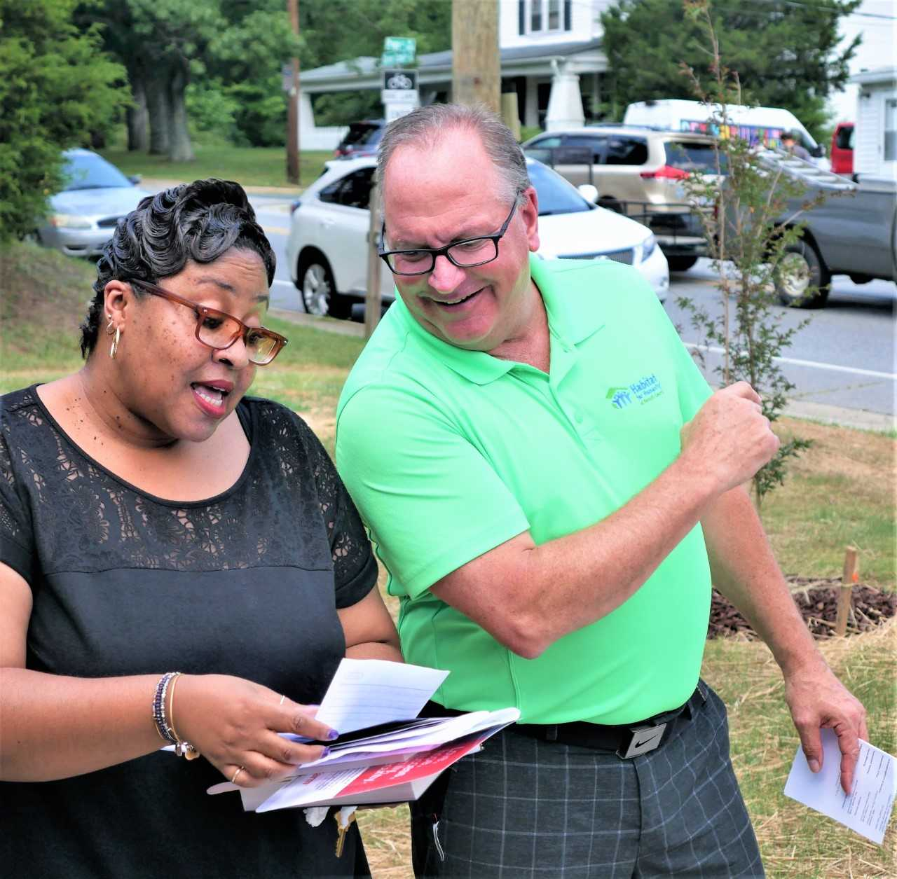 Khadijah Shabazz, left, and Mike Campbell, executive director of Habitat for Humanity of Forsyth County, lead the dedication of a new home in Winston-Salem for Shabazz and her daughter Sakile.