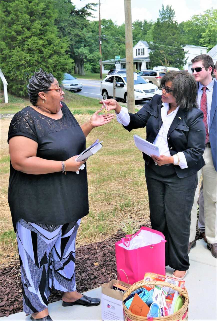 Fentress Gerald of the State Employees Credit Union, right, presents Khadijah Shabazz with the keys to her new home.