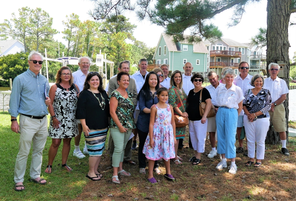 In the back yard of their new home, Pat and Savannah Moncur, center front, stand with some of the people who helped to secure her future. At left is Greg Kirkpatrick, CEO of Habitat for Humanity North Carolina.